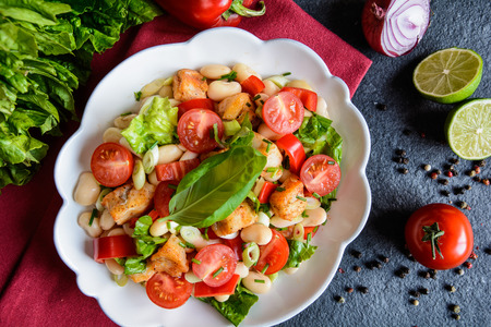 Vegetable salad with white beans, fried fish pieces, red pepper, green onion and chive Stock Photo