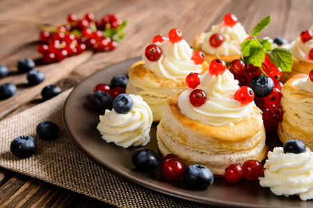 profiterole: Fresh cream puff cakes with red currants and blueberry