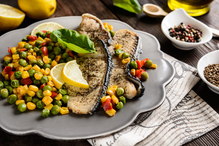 Fried blue shark steak with steamed pea, corn and red pepper Stock Photo