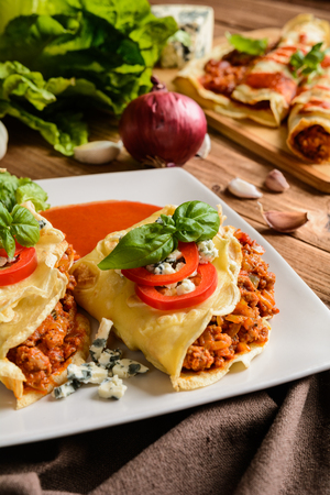 Pancakes stuffed with Bolognese filling - minced beef, pepper, onion, garlic and basil with tomato sauce Stock Photo