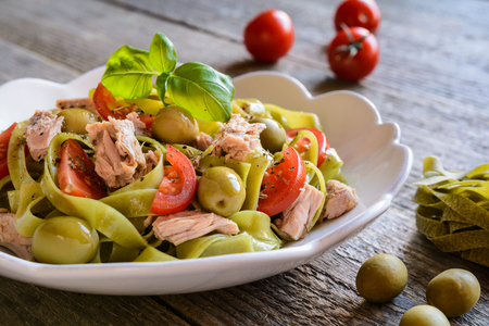 Spinach Tagliatelle pasta with tuna fish, tomato and green olives Stock Photo - 63694301