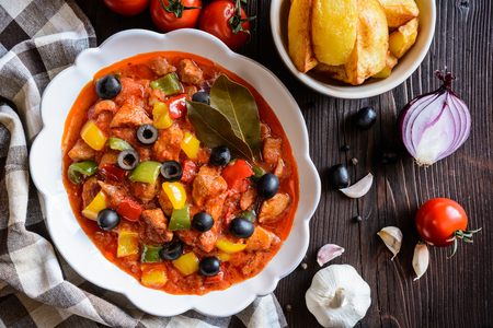 Ragu with sliced pork, tricolor pepper, black olives and fried potatoes Stock Photo