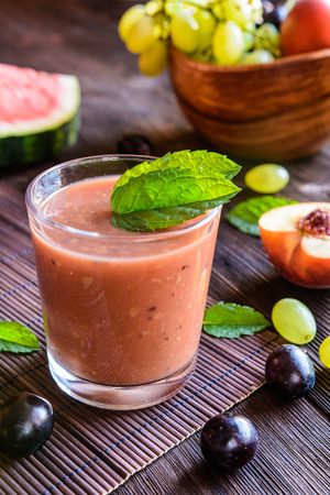 Organic smoothie with grape, watermelon and peach in a glass jar