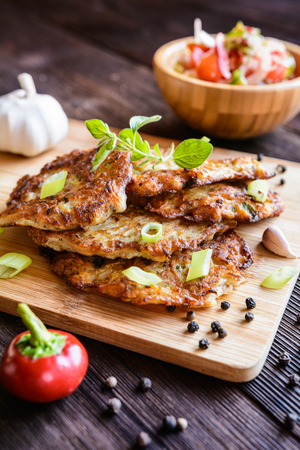 Fried celery pancakes with onion, garlic, parsley and vegetable salad