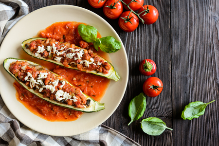 filled: Stuffed zucchini with pork, pepper, garlic, onion and cheese garnished with tomato salsa Stock Photo