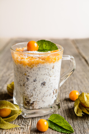 Probiotic yogurt with chia seeds, coconut, honey and physalis puree in a glass jar