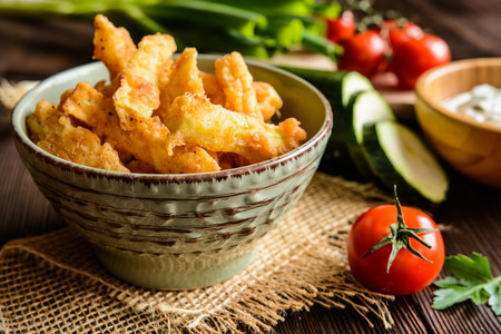 Deep - fried zucchini fries with sour cream dipping sauce