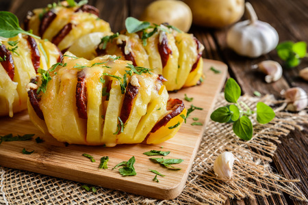 smoked sausage: Baked potatoes stuffed with smoked sausage slices, cheese, garlic and herbs Stock Photo