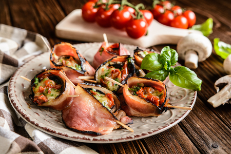 quick snack: Bacon wrapped mushrooms stuffed with mozzarella, sun dried tomatoes and herbs Stock Photo