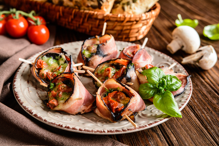 Bacon wrapped mushrooms stuffed with mozzarella, sun dried tomatoes and herbs Stock Photo