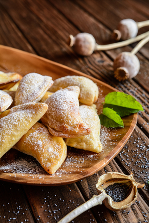 poppy seeds: Sweet baked dumplings stuffed with poppy seeds and sprinkled with powdered sugar Stock Photo