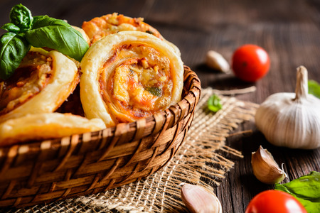 calorie rich food: Baked puff pastry rolls stuffed with tofu, mozzarella, tomato sauce, garlic and basil Stock Photo