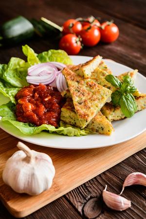 Fried savory zucchini pancakes, served with tomato salsa