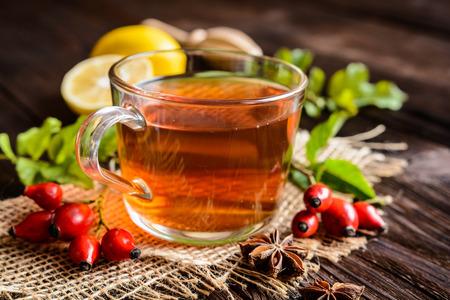 Cup of rosehip tea with lemon in a glass jar 免版税图像