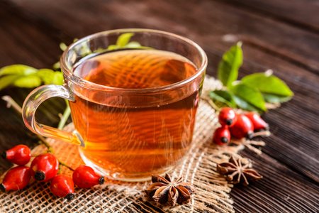 Cup of rosehip tea with lemon in a glass jar Stock Photo