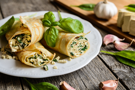Savory pancakes stuffed with tofu, spinach, onion and garlic Stock Photo - 64908279