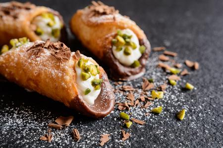 Cannoli Siciliani - traditional dessert stuffed with ricotta cream and pistachios Banco de Imagens
