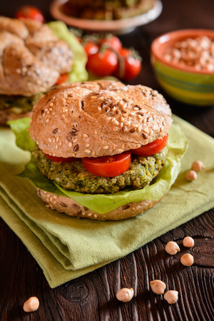 Vegetarian whole wheat burger with chickpeas - spinach fritter, lettuce and tomato garnish