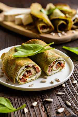 Savory spinach pancakes stuffed with Feta cheese, curd, sun dried tomato and sunflower seeds