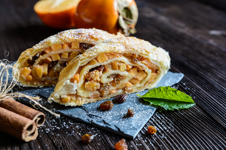 Sweet strudel stuffed with persimmons, raisins, walnuts and cinnamon Stock Photo