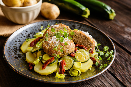 Fried minced pork patties meat with steamed potato, zucchini, leek and sun dried tomato