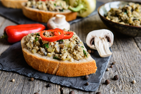 stirred: Scrambled eggs with mushrooms, onion, pepper and parsley on bread slices Stock Photo