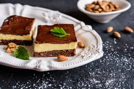 Nanaimo bars - traditional Canadian dessert with wafer crumbs, almond, walnut and cocoa layer, vanilla custard filling and chocolate topping Stock Photo