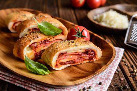 Traditionele Italiaanse Stromboli gevuld met kaas, salami, groene ui en tomatensaus Stockfoto - 69566684