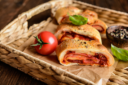 filled roll: Traditional Italian Stromboli stuffed with cheese, salami, green onion and tomato sauce