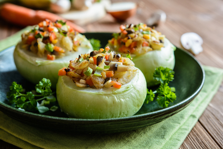 Vegetarian roasted kohlrabi stuffed with mushrooms, onion, eggs, and carrot