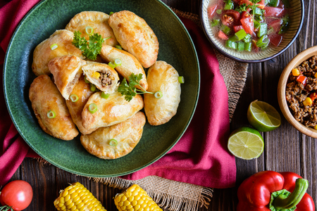 Traditional Empanadas stuffed with minced beef, pepper and corn, served with Aji Picante sauce Stock Photo