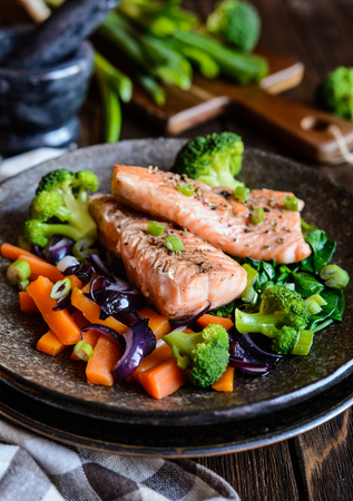 Fried salmon steaks with steamed carrot, broccoli, onion and spinach Stock Photo