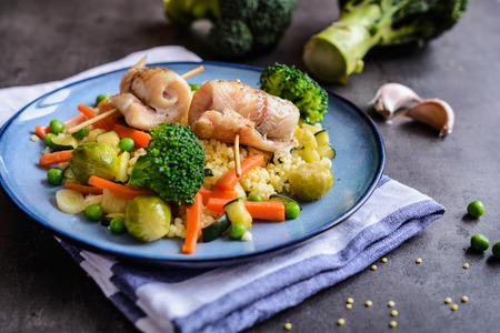 Roasted cod fillets rolls served with millet and steamed broccoli, carrot, brussels sprouts and zucchini Stock Photo