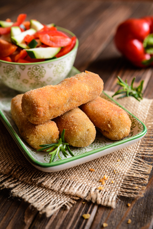 Fried chicken croquettes served with vegetable salad