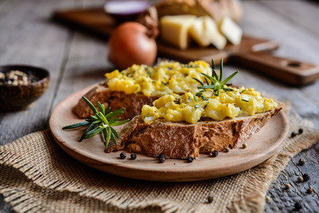 whole wheat toast: Whole meal bread slices with scrambled eggs, cheese, onion and herbs