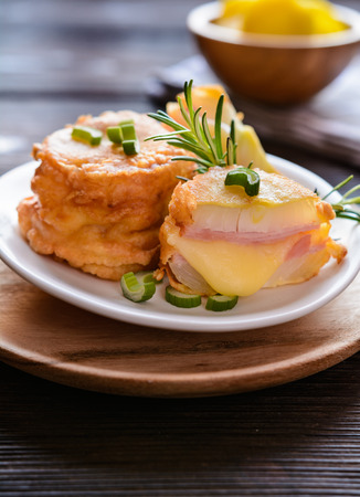 Deep fried onion slices coated in batter, stuffed with ham and cheese