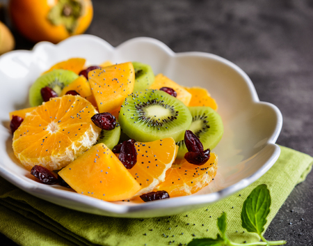 Refreshing fruit salad with Minneola tangelo, kiwi, persimmons, cranberries and sprinkled with poppy seeds Stock Photo
