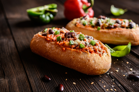 Baked baguette stuffed with mixture of minced pork, tomato sauce, beans, green bell pepper, onion, garlic and sprinkled with cheese