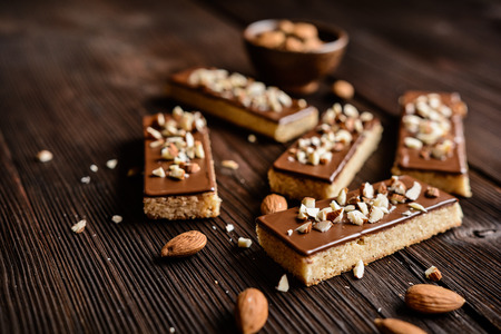Baked almond shortbread sticks with chocolate and chopped nuts glaze Reklamní fotografie