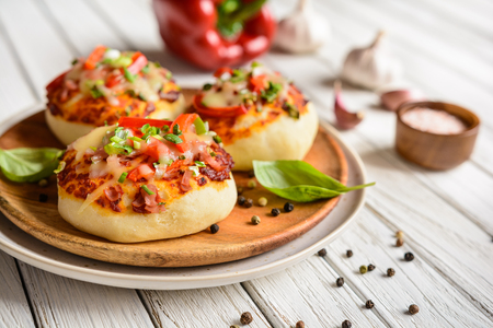 Homemade mini pizza buns topped with tomato sauce, ham, bell pepper, green onion, garlic and cheese