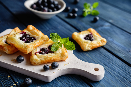 Baked small square cakes topped with ricotta and blueberry