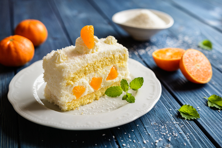 Coconut cake with whipped cream and tangerine Stock Photo