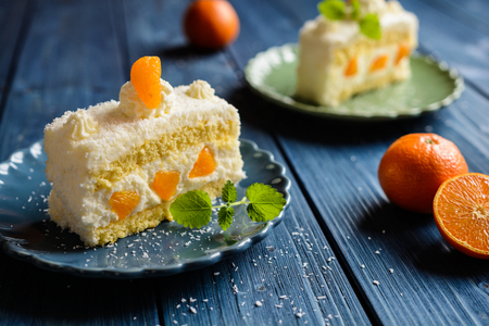 Coconut cake with whipped cream and tangerine Imagens