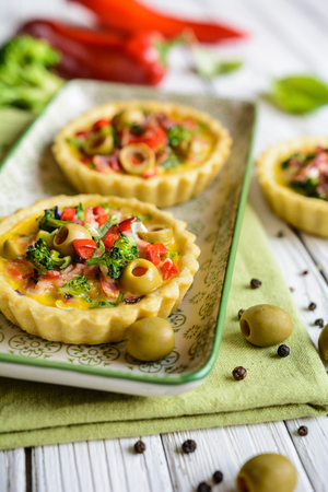 Salty tartlets stuffed with bacon, bell pepper, broccoli, cheese, onion, egg and olives