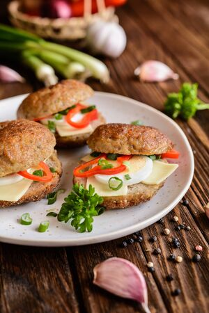 Fried patty filled with cheese slices, egg, bell pepper and scallion