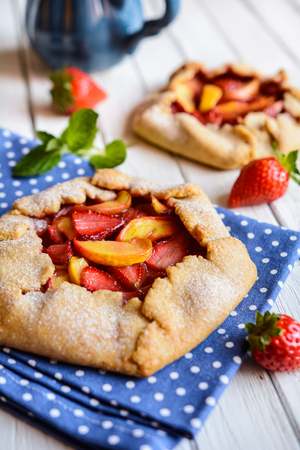 Traditional French Galette pie filled with strawberry and peach