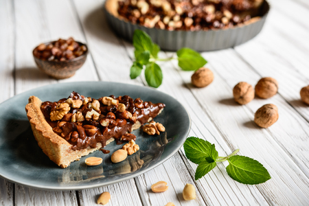 Delicious tart filled with chocolate, walnut, peanut, dried cranberry and raisins