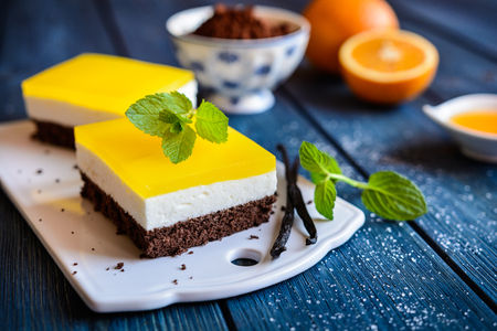 Delicious chocolate cake bars with mascarpone layer and orange jelly topping