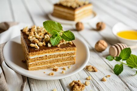 A slice of layered honey cake with chocolate and walnut topping
