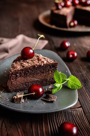 Chocoladecake gevuld met cacaoslagroom en versierd met chocoladeschilfers en kersen
